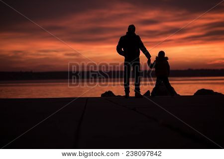 Father Holding Hands With His Son As They Stand Silhouetted Against A Colorful Vivid Orange Ocean Su