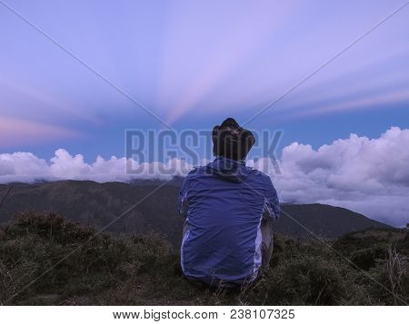 A Male Who Wears A Blue Jacket Sitting On The Ground And Watching The Amazing Anti-crepuscular Rays