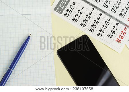 Pen, Notebook, Calendar And Phone Are On The Table