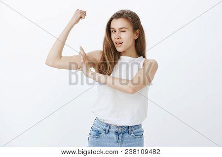 Girl Is Confident In Strength. Portrait Of Charming Flirty European Woman With Fair Hair, Raising Ha