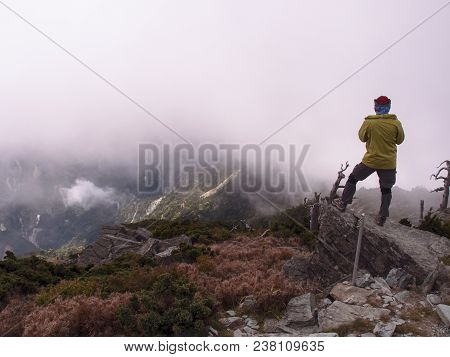 A Brave Asian Male Standing On A Peak And Enjoying The View Of Mountains With Thick Fog. Looking A L