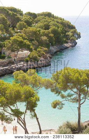 Cala D'or, Mallorca - August 2016 - A View Onto The Beach Of Cala D'or Through A Few Trees