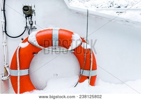 Lifebuoy ring on white boat in winter covered with snow. Safety equipment on the boat. Orange life buoy on a sailing boat