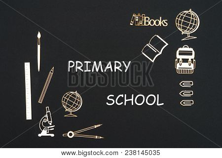 Concept back to school, text primary school with school supplies chipboard miniatures placed on blackboard poster