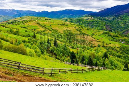 Wooden Fence Along The Grassy Hillside. Beautiful Springtime Landscape Of Carpathian Mountains On A