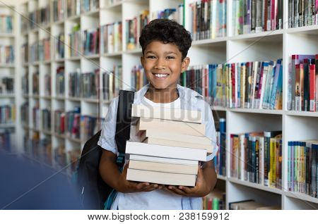 Middle eastern boy holding a stack of books against multi colored bookshelf in library. Portrait of happy arab schoolboy with backpack at school. Happy young indian child holding heap of books.