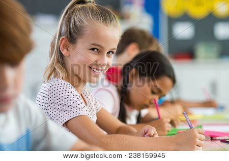 Happy beautiful schoolgirl doing classwork while looking at camera. Smiling scholar girl sitting at school desk with her classmates in background. Young pretty kid enjoying study in elementary school.
