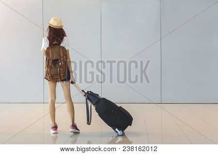 Young Woman Is Standing Near Window At The Airport And Watching Plane Before Departure. She Is Stand