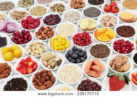 Health food for a healthy heart concept with super food of fish, fruit, vegetables, pulses, nuts, seeds, grains, cereals with herbs and spice used in alternative herbal medicine.