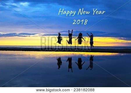 Stock Photo - Silhouette Of A Happy Ladies Jumping To 2018 New Year On The Beach With A Beautiful Su