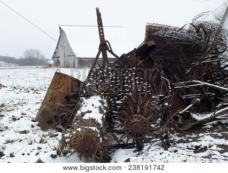 Pile Of Vintage Rusty Farm Implements And Equipment In Snow Covered Field With Barn In Background