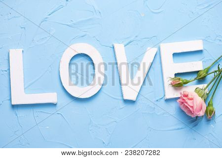 Word Love Made From White Wooden Letters And Pink Roses Flowers On  Light Blue Textured Background.