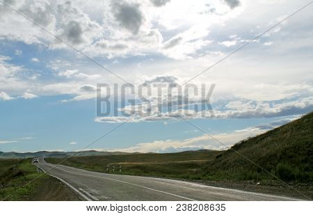 Road In Steppe. Wide Steppe With Yellow Grass Under A Blue Sky With White Clouds Sayan Mountains Sib