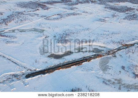 The Building Of Gas Or Oil Pipeline In Western Siberia In Winter, View From Above During Flight On H