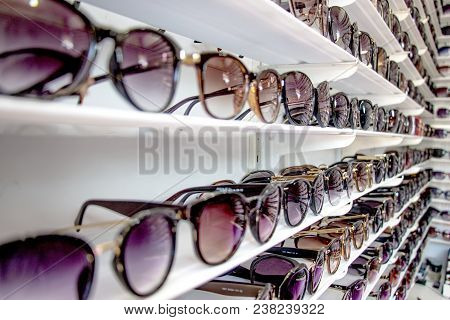 Sunglasses, Shades, Eyeglasses Display Backlight Stand At Unidentified Fashion Shop Shelf In Airport