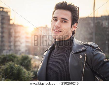 One Handsome Young Man In Urban Setting In Modern City, Standing, Wearing Black Leather Jacket And J