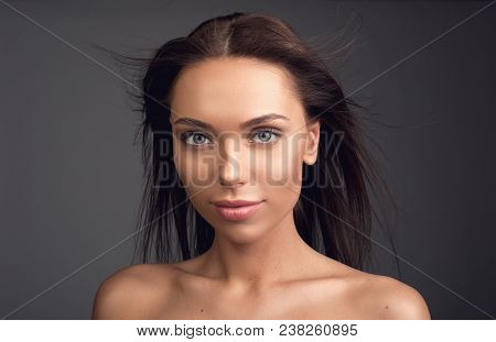 Haircare Concept. Portrait Of Appealing Girl Having Long Flattering Locks. She Is Staring At Camera