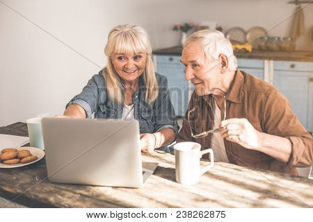 Excited Mature Pensioners Watching Video On Laptop In Kitchen. They Are Drinking Tea With Cookies An