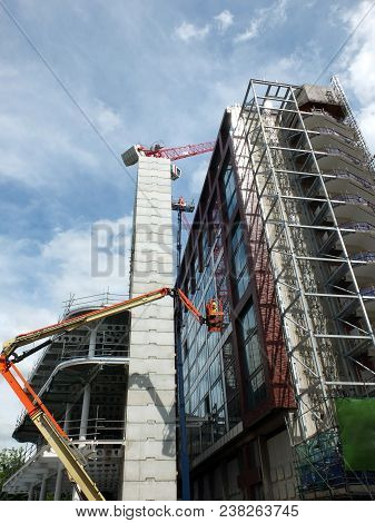 large modern high rise construction site with telescopic cranes poster