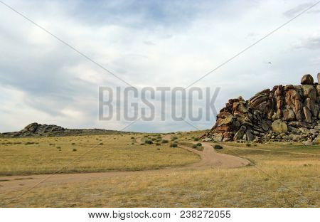 Wide Steppe With Yellow Grass Under A Blue Sky With White Clouds Sayan Mountains Siberia Russia.