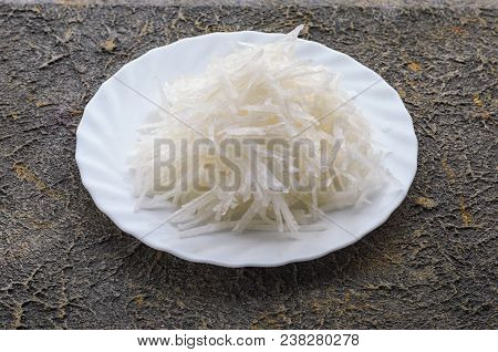 White Plate With A Reliable Daikon Close-up On A Concrete Background