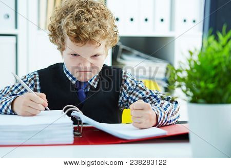 Little Angry Curly Caucasian Boy Like Businessman Doing Paperwork In Office.