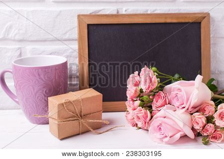 Pink Roses Flowers, Empty Blackboard,  Box With Present And Violet Cup On White Wooden Background. F
