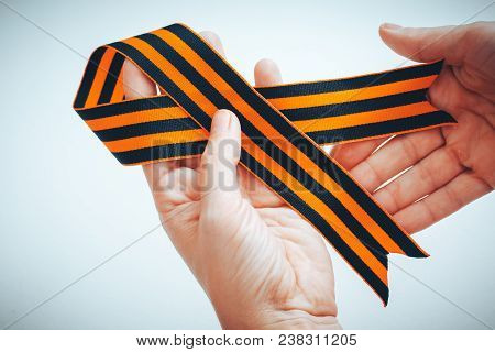 Orange And Black Striped Ribbon Symbol On May 9 In Hands. The Symbol Of The Great Victory Over The N