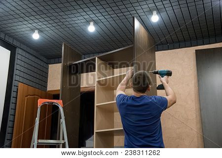 Assembling A Wooden Brown Cabinet At Home Using A Drill And A Screwdriver