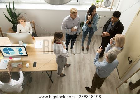 Multiracial People Of Different Age Working On Computers Talking In Modern Coworking Space, Diverse