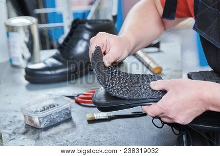 Shoemaker repair shoe. Glueing the sole for male footwear