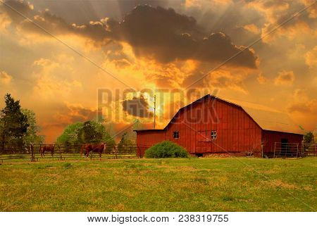 A Rustic Red Barn On A Farm With Horses Out In The Pasture During A Dramatic Cloudy Golden Sunset.