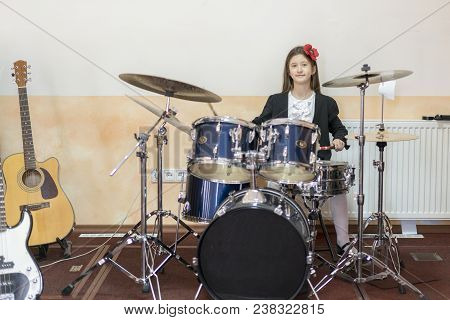Young Caucasian Teenage Girl Plays The Drums. Girl Playing The Drum Set.