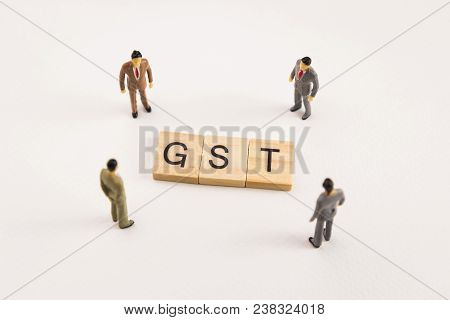 Miniature Figures Businessman : Meeting On Gst Letters By Wooden Block Word On White Paper Backgroun