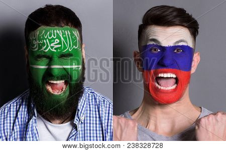 Emotional Soccer Fans With Painted Saudi Arabia And Russia Flags On Faces. Confrontation Of Football