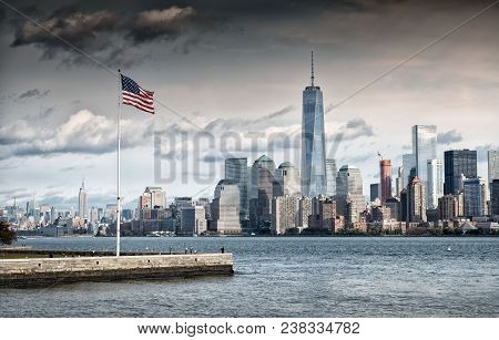 Grey Cloud Hangs Above American Flag Overlooking The New York City Financial District