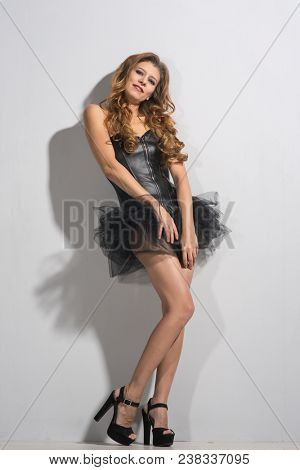 beautiful young woman in a corset and a skirt on a gray background