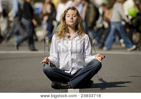 woman meditating yoga in lotus position on busy urban street