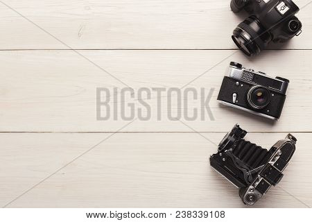 Three Different Photo Cameras On White Table, Top View. Comparison Of Different Generations Of Photo