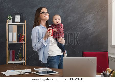 Happy Beautiful Business Mom Working In Office While Spending Time With Her Cute Baby And Drinking C