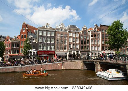 AMSTERDAM - JULY 10: Canals of the Amsterdam city on July 10, 2016 in Amsterdam, Netherlands. The historical canals of the city surrounded by traditional dutch houses is a landmark of Amsterdam.