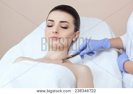 poster of The cosmetologist makes the procedure Microdermabrasion of the facial skin of a beautiful, young woman in a beauty salon.Cosmetology and professional skin care.