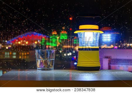 Luminous Hand Lantern Standing Near A Wet Window On The Background Of Illuminated Buildings Of Sochi
