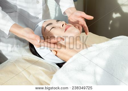 Portrait of blissful  Asian woman enjoying gentle facial massage while lying on soft bed in modern beauty salon poster