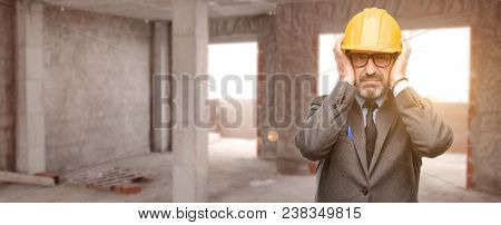 Senior architect or engineer covering ears ignoring annoying loud noise, plugs ears to avoid hearing sound. Noisy music is a problem. at unfinished building