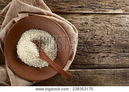 Raw Arborio Risotto Short-grain Rice On Clay Plate With Wooden Spoon, Photographed Overhead On Wood