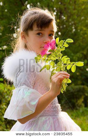 Little Girl Holding Rose Flower To Her Face