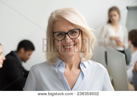 Portrait Of Smiling Senior Businesswoman Wearing Glasses With Businesspeople At Background, Happy Ol