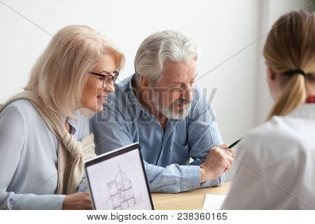 Older Couple Reading Contract At Meeting With Real Estate Agent Considering New Home Purchase, Realt