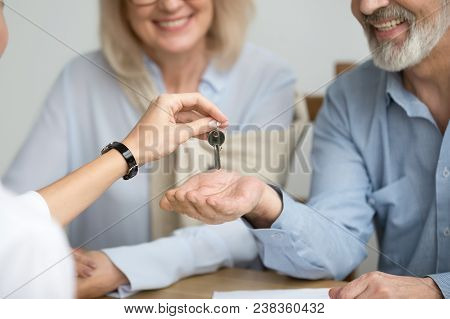 Realtor Giving Senior Aged Couple Key To New House At Meeting, Happy Older Real Estate Owners Make P